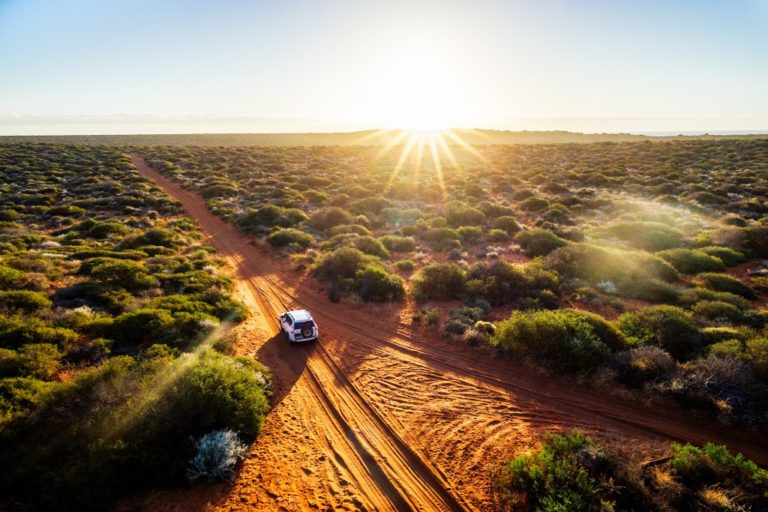 Hot sun shining over the unpaved road
