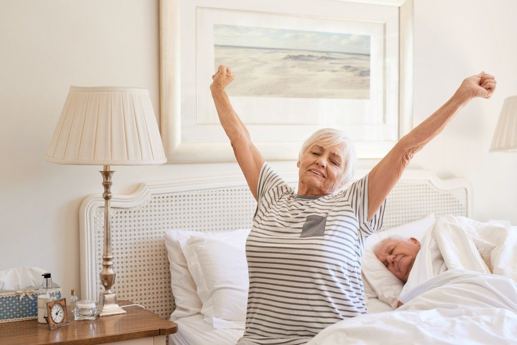 Senior woman yawning in the morning with husband sleeping