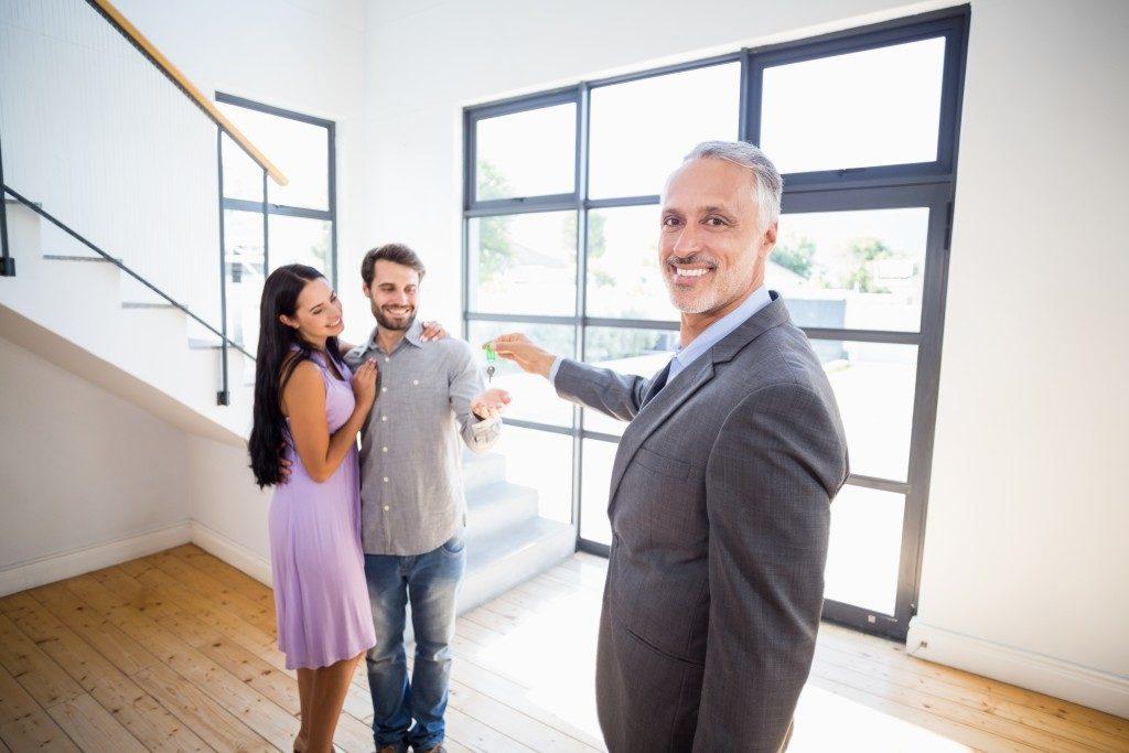 broker giving keys to couple