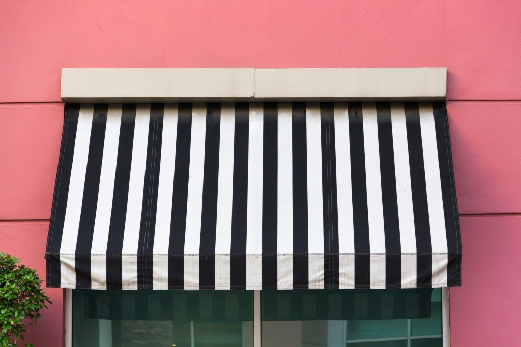 black and white awning over glass window on pink wall
