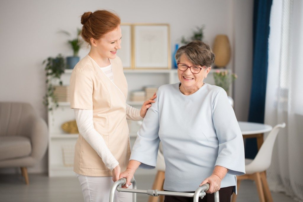 Caregiver assisting a woman to walk