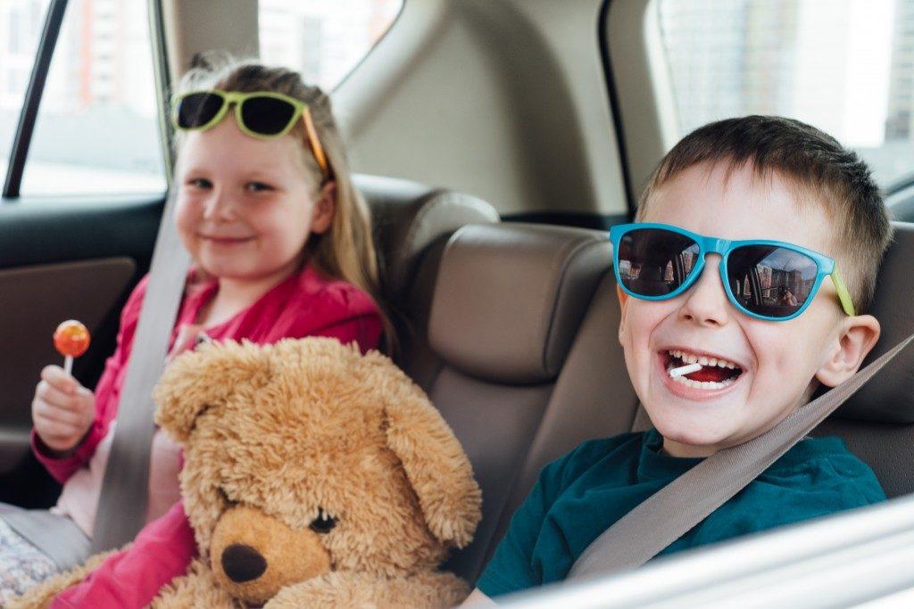 children inside the car with a teddy bear