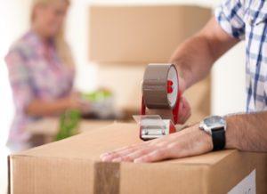 man putting packing tape on box
