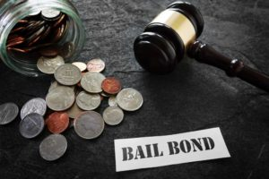 coins gavel and bail bond on paper