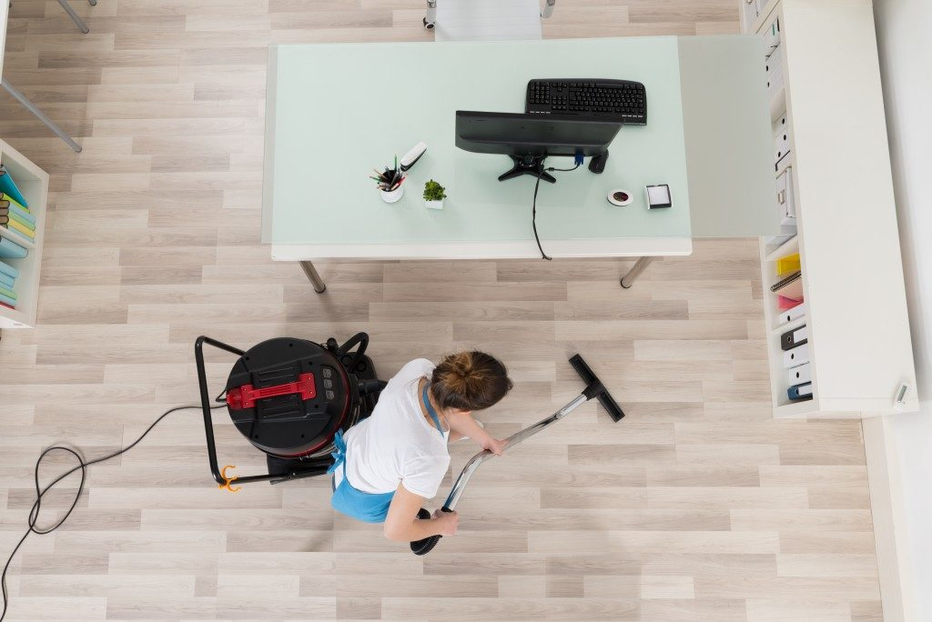 Woman cleaning floor with vacuum