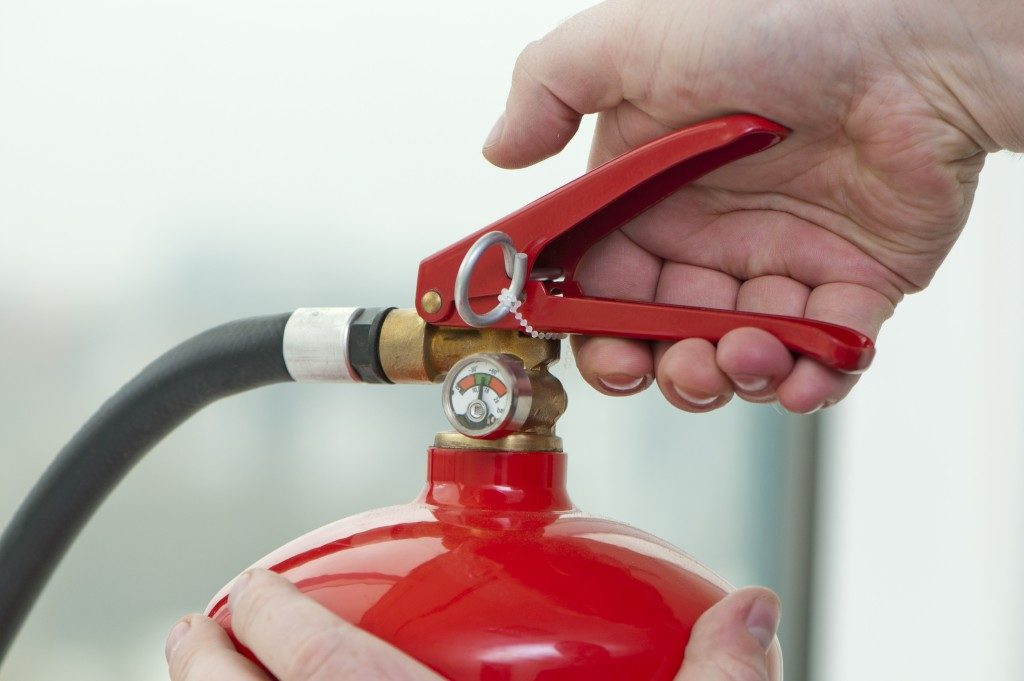 Hand pressing the trigger on a fire extinguisher