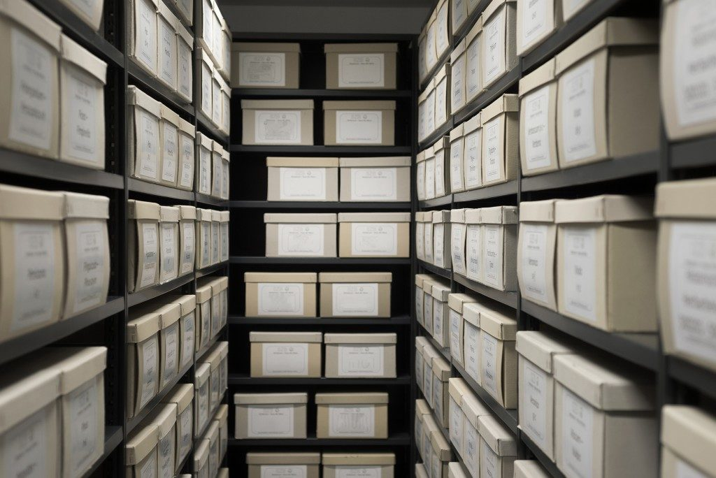 Archive evidence police depository cardboard box black shelves with white office boxes card file