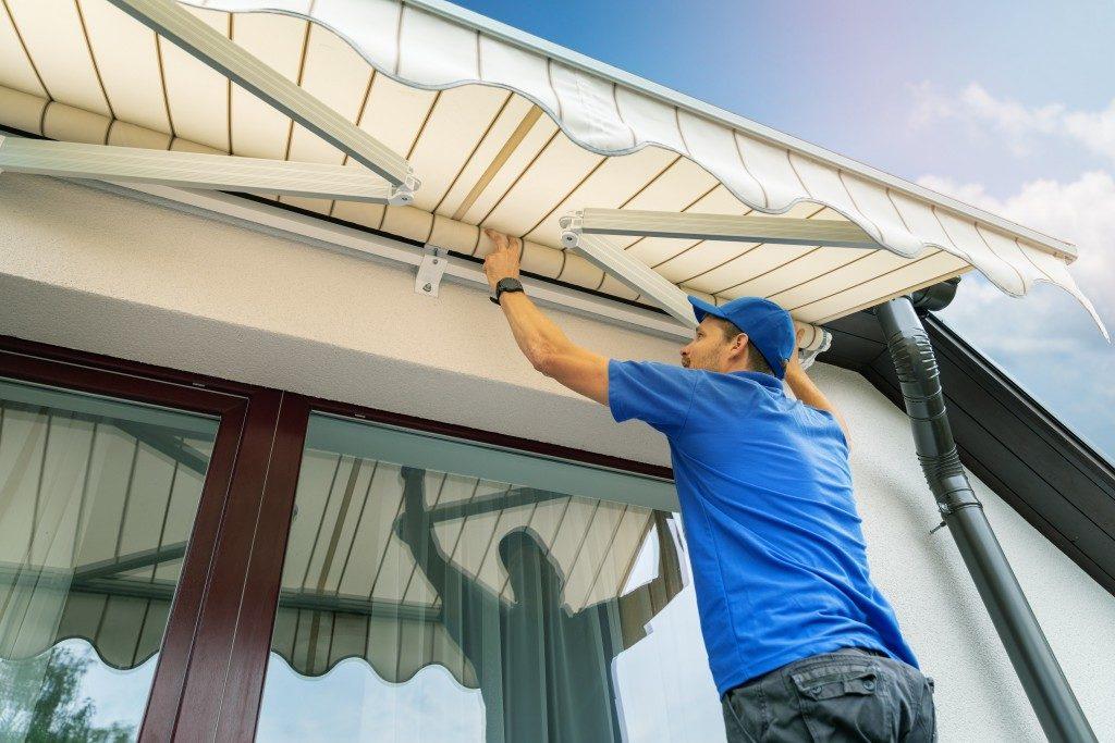 man installing an awning