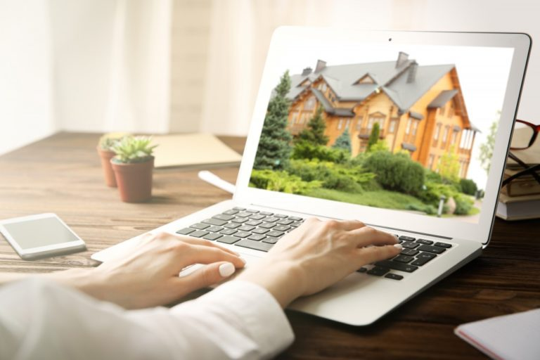 woman looking at a house on the laptop