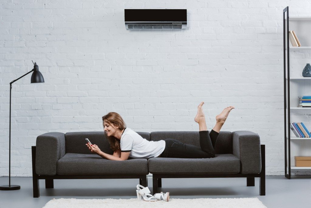 woman laying on the couch with her phone