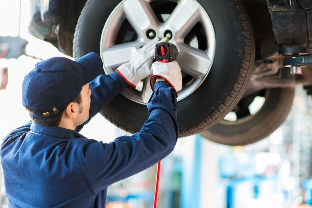 man fixing car tires
