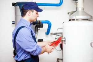 man repairing a water heater