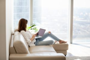 woman sitting on a couch while using a laptop