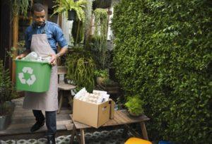 man carrying a recycling bin