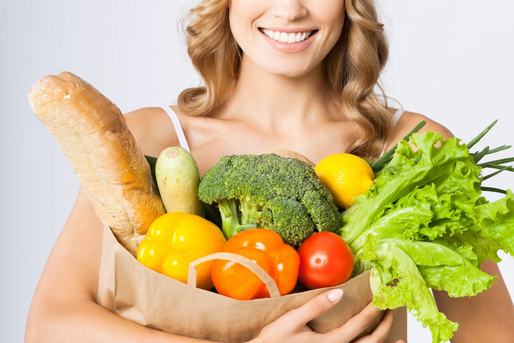 holding grocery shopping bag with healthy vegetarian raw food