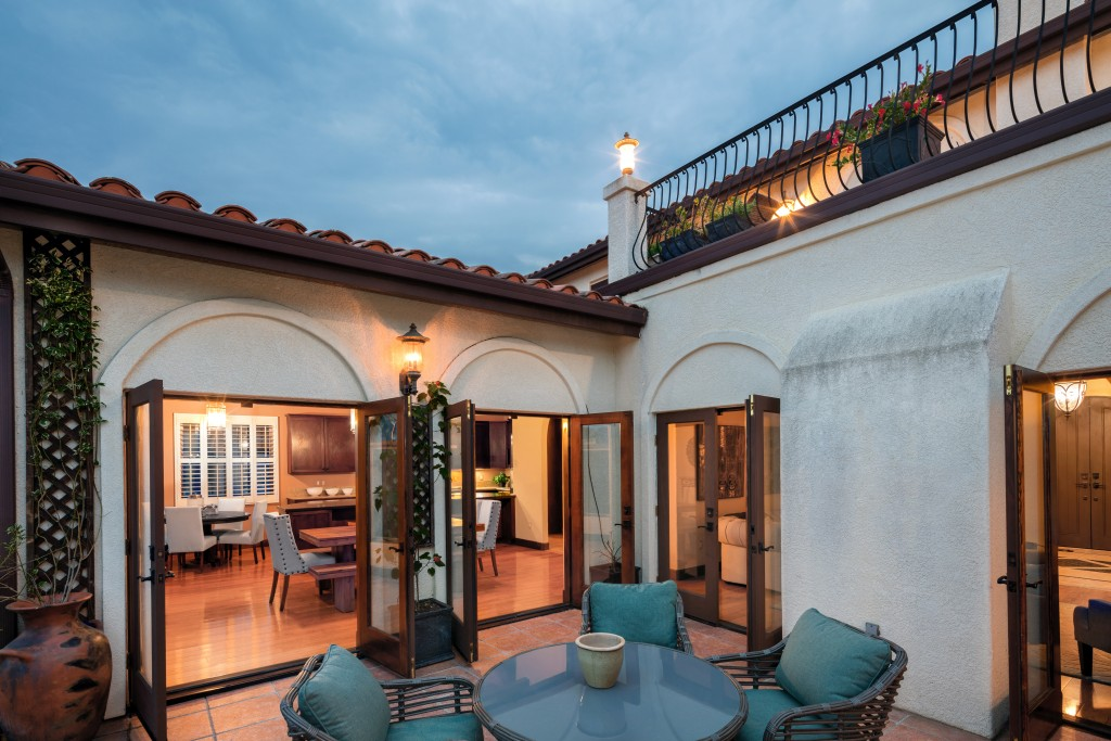 Amazing Mediterranean home at twilight with patio and open french doors. Spanish style home at twilight and open floor plan.