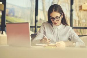 Female writing beside her laptop