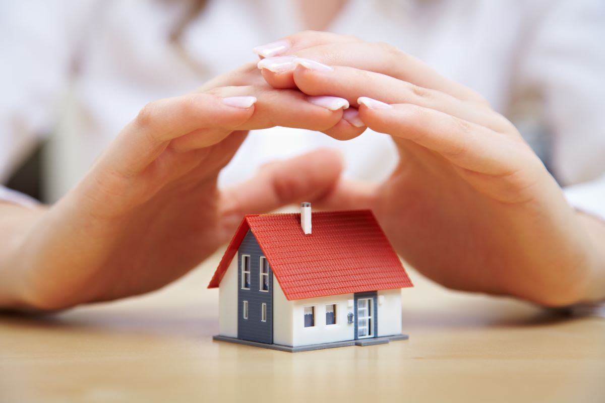 hands hovering above a tiny house model