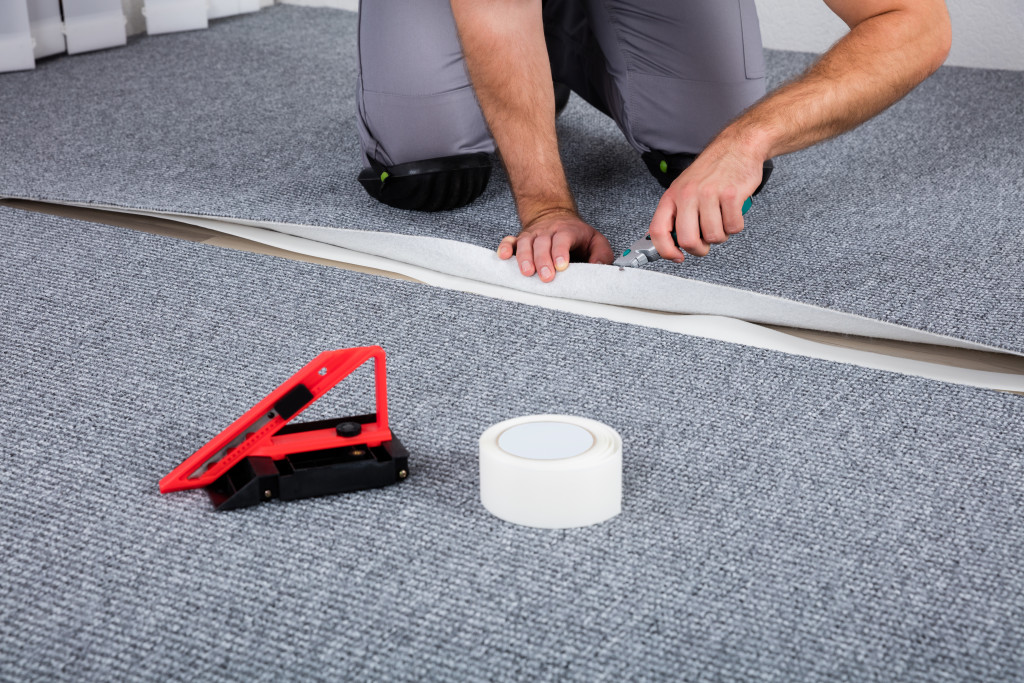 a person installing carpeting