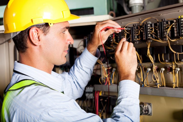 man repairing the wires inside a fuse box