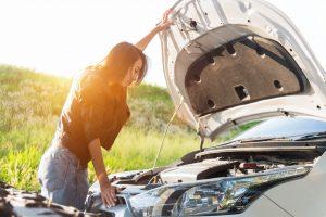 woman looking at broken down car